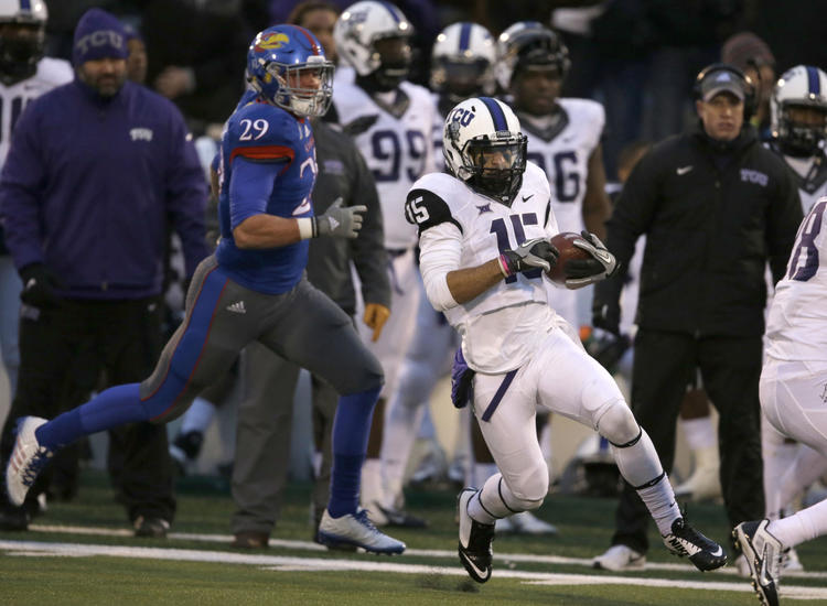 TCU punt returner Cameron Echols-Luper (15) cuts behind blockers and ahead of Kansas special teams player Joe Dineen Jr. (29) on his way for a touchdown during the second half of an NCAA college football game in Lawrence, Kan., Saturday, Nov. 15, 2014. TCU defeated Kansas 34-30.