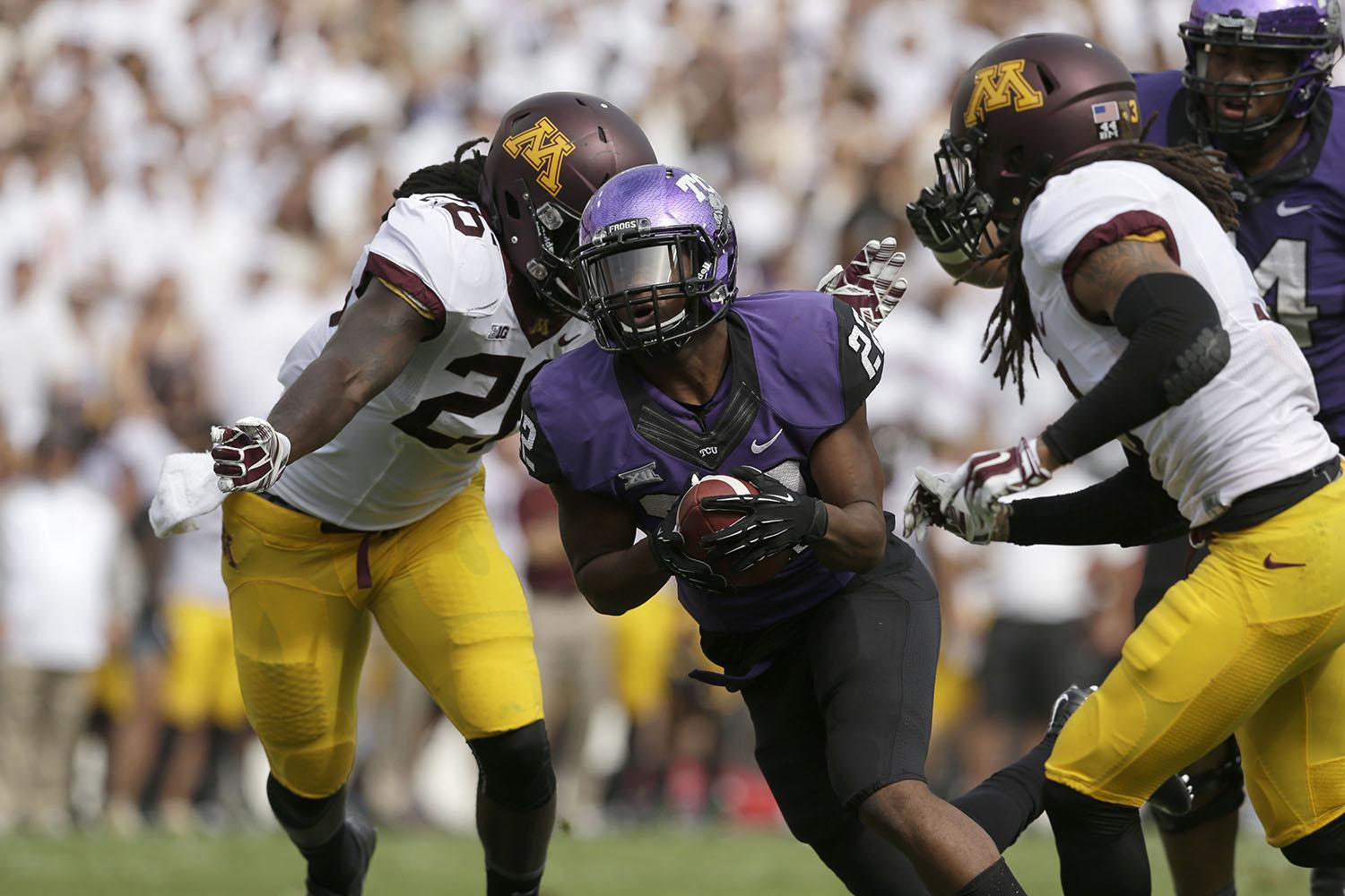 TCU running back Aaron Green (22) finds a hole against Minnesota defense during an NCAA college football game, Saturday, Sept. 13, 2014, in Fort Worth, Texas.(AP Photo/LM Otero)