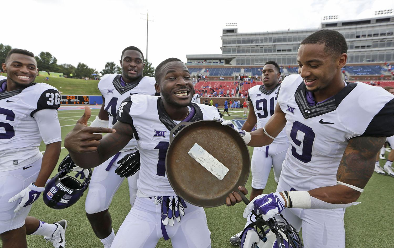 """TCU wide receiver David Porter (14) shows off the famed iron skillet with teammate and fellow wide receiver Josh Doctson (9) after their 56-0 win over SMU in an NCAA college football game  Saturday, Sept. 27, 2014, in Dallas.  The """"skillet"""" goes the the winner of the SMU-TCU game and has been a tradition since 1915. (AP Photo/LM Otero)"""