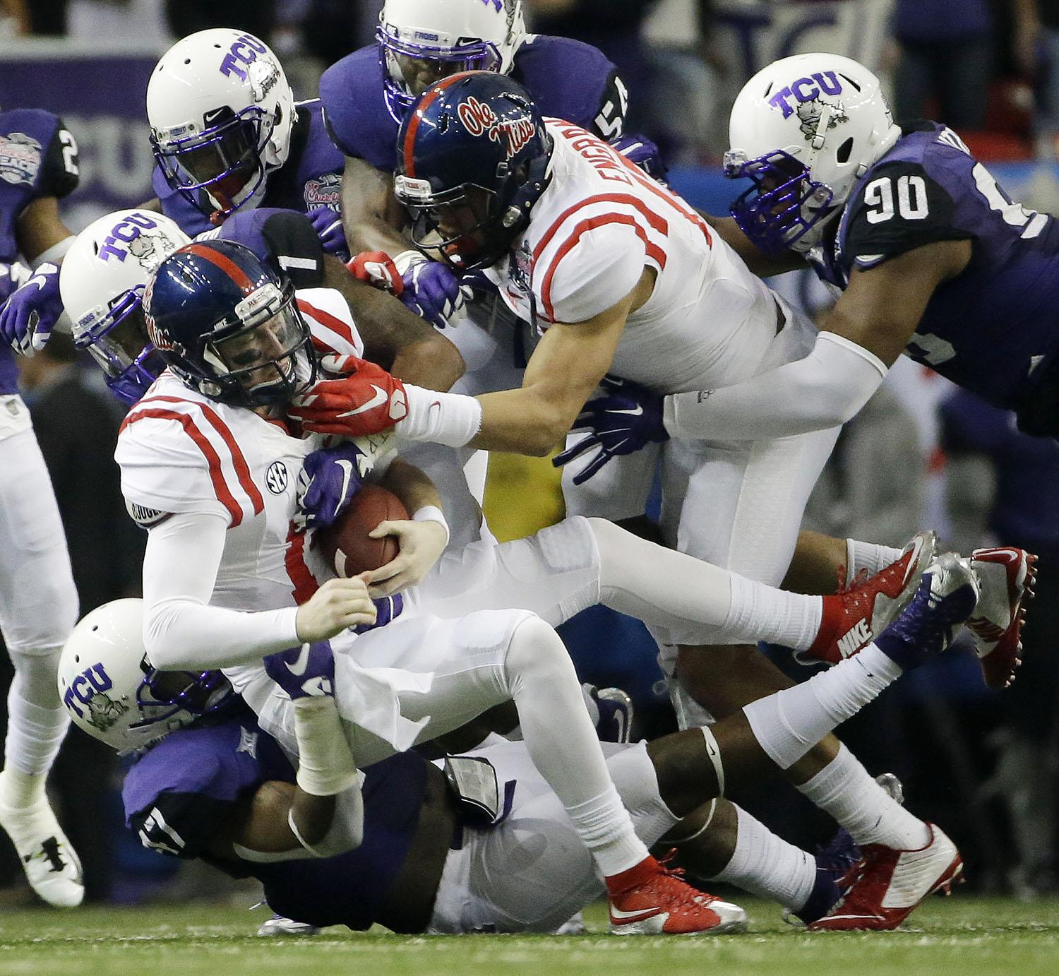 Mississippi quarterback Bo Wallace (14) is sacked my TCU during the first half of the Peach Bowl NCAA football game, Wednesday, Dec. 31, 2014, in Atlanta. (AP Photo/David Goldman)