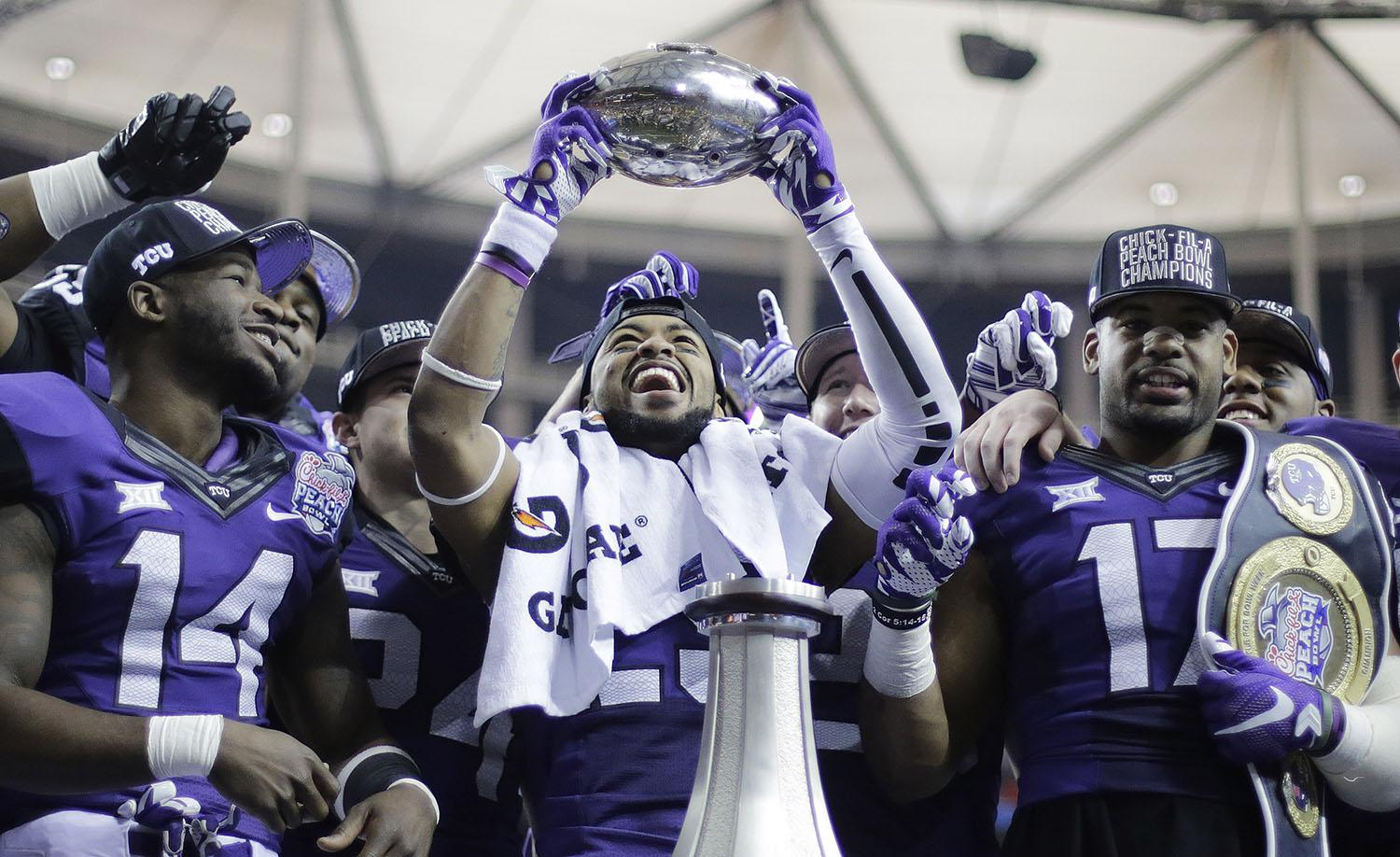 TCU safety Michael Downing holds part of the Peach Bowl trophy after the second half of the Peach Bowl NCAA football game against Mississippi, Wednesday, Dec. 31, 2014, in Atlanta. TCU won 42-3. (AP Photo/David Goldman)