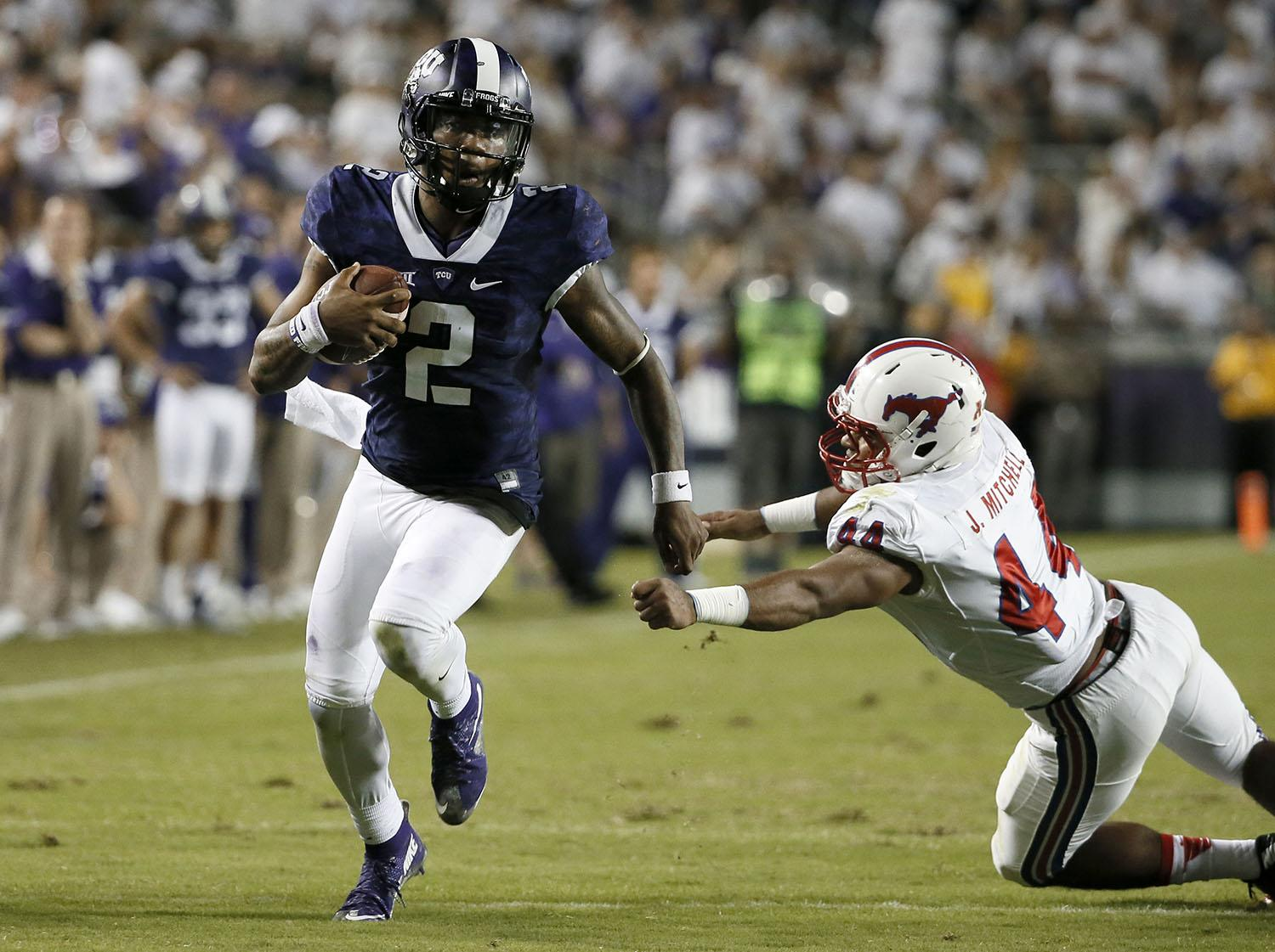 TCU quarterback Trevone Boykin (2) escapes a tackle attempt by SMU's Jackson Mitchell (44) in the second half of an NCAA college football game Saturday, Sept. 19, 2015, in Fort Worth, Texas. Boykin threw for 454 yards and five touchdowns and added a highlight scoring run when he ducked out of a sack as third-ranked TCU held on for a 56-37 victory over SMU on Saturday night. (AP Photo/Tony Gutierrez)