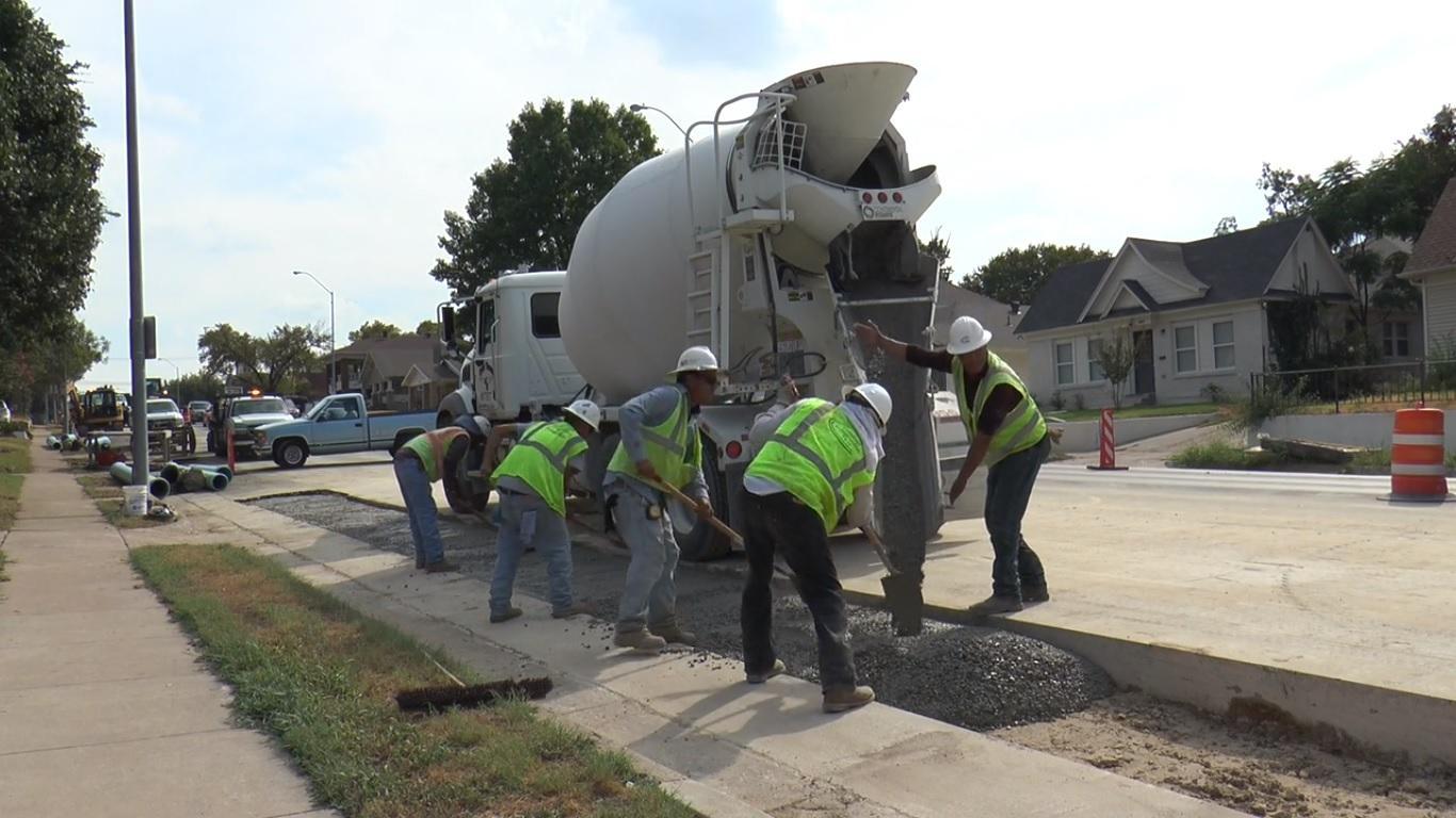 Construction workers pour concrete on University Drive by TCU.