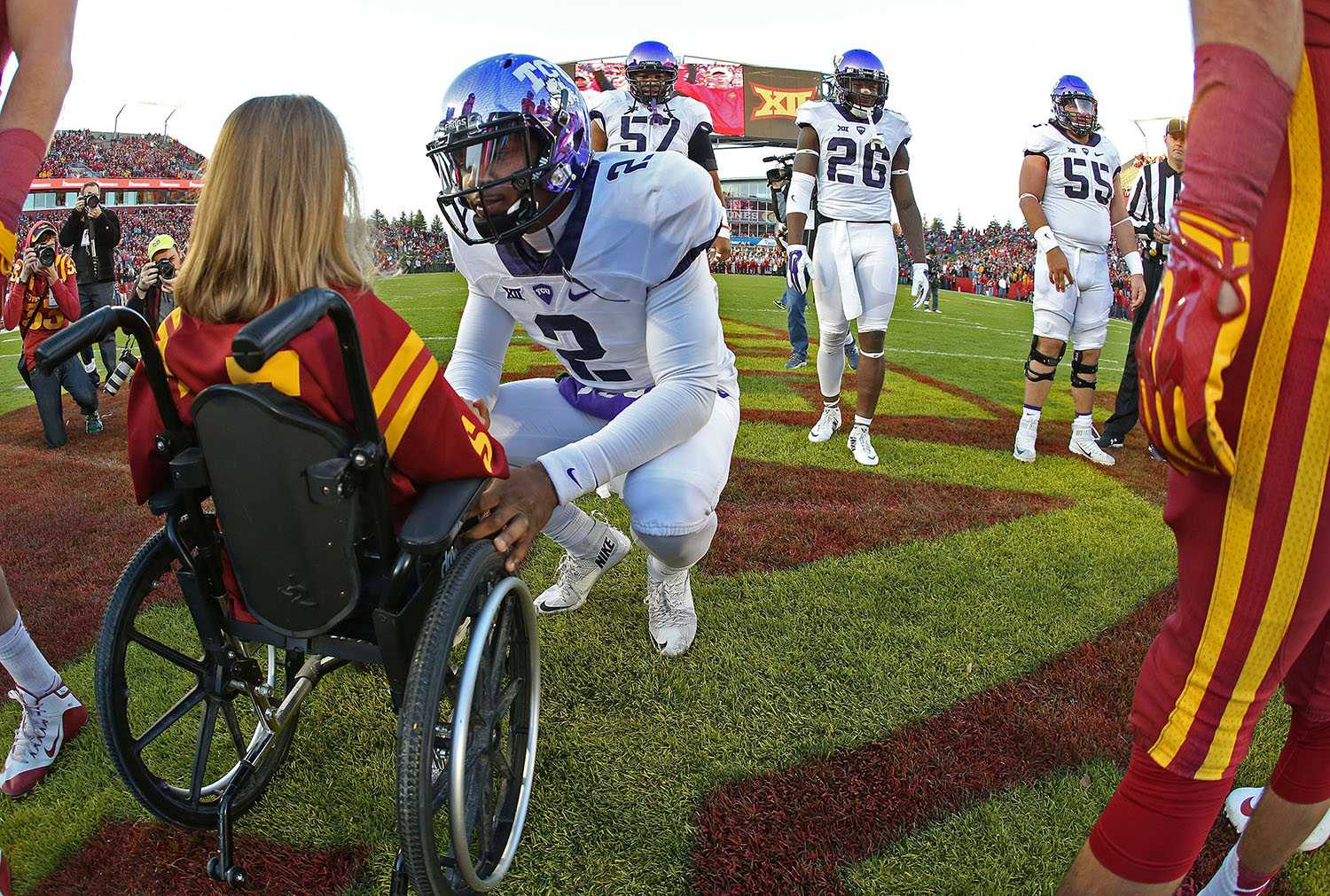 At the coin flip, TCU Horned Frogs quarterback Trevone Boykin (2) knelt to ask Abby Faber, an Iowa State honorary captain at the flip as a guest, her name. The TCU Horned Frogs play the Iowa State Cyclones in Ames, Iowa, Saturday, October 17, 2015.