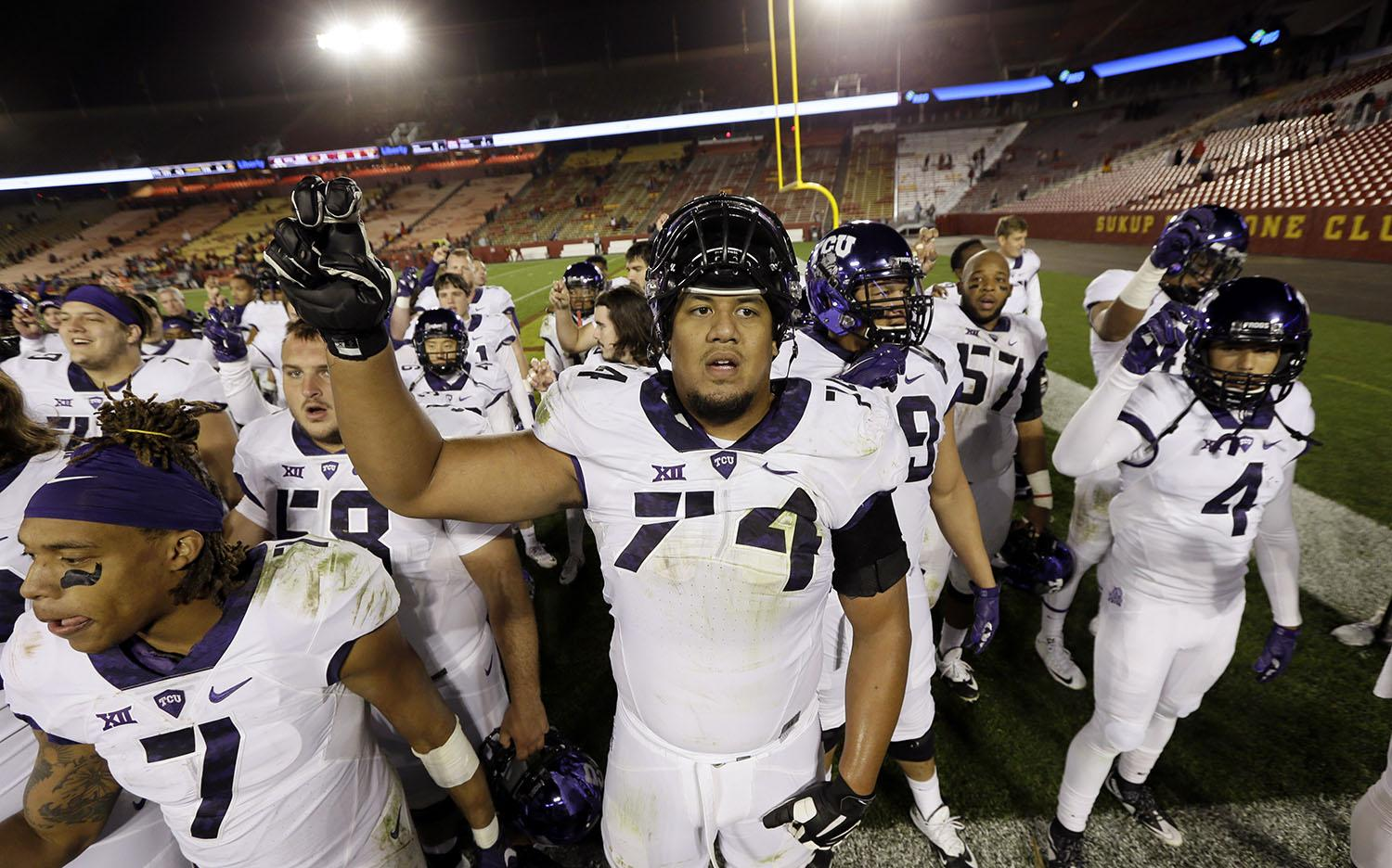 TCU offensive tackle Halapoulivaati Vaitai, center, celebrates with teammates after their 45-21 victory over Iowa State in an NCAA college football game, Saturday, Oct. 17, 2015, in Ames, Iowa. (AP Photo/Charlie Neibergall)