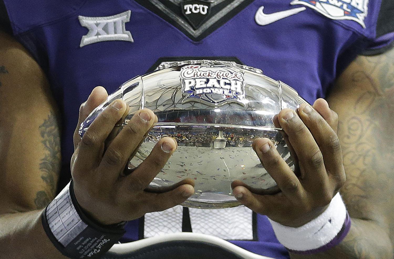 TCU quarterback Trevone Boykin holds part of the Peach Bowl Tropy after the second half of the Peach Bowl NCAA football game against Mississippi, Wednesday, Dec. 31, 2014, in Atlanta. TCU won 42-3. (AP Photo/David Goldman)