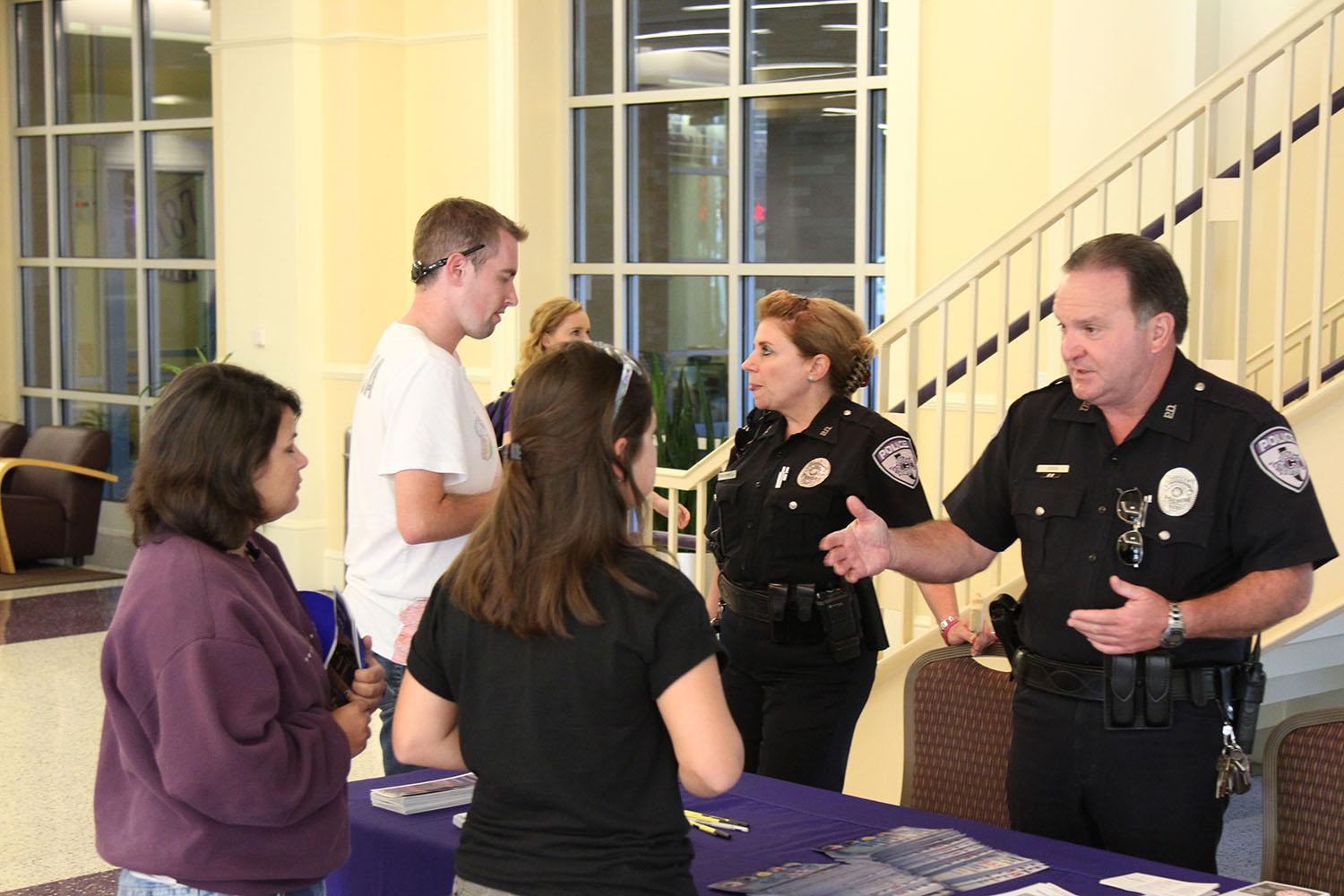 TCU Police Officers Pam Christian (left) and George Steen (right) inform students about crime prevention on campus.