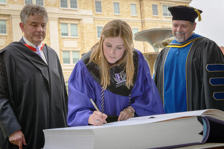 An honors laureate is accompanied by Provost Nowell Donovan (left). Photo courtesy of Lauren Nixon of the Honors College.