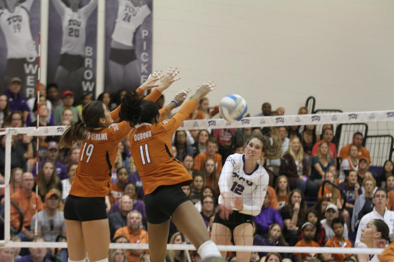 Outside hitter Ashleigh Martin spikes a ball past the Longhorn's front line blockers. TCU defeated Texas in straight sets Wednesday (25-19, 25-19, 25-20).