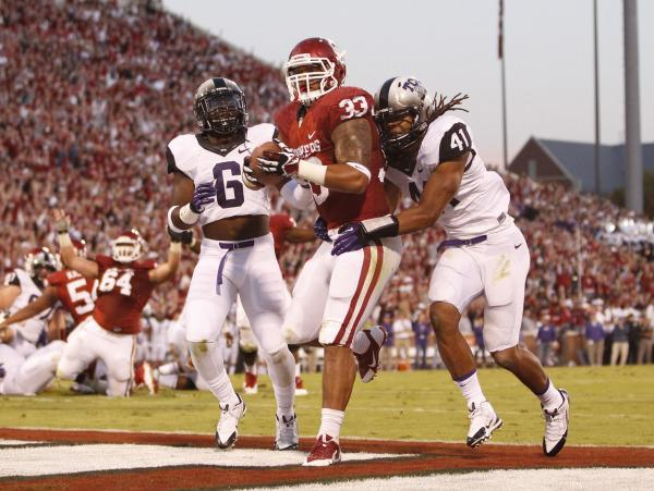 Oklahoma Sooners fullback Trey Millard (33) runs for a touchdown in the second quarter against the TCU Horned Frogs safety Elisha Olabode (6) and linebacker Jonathan Anderson (41) at Gaylord Family - Oklahoma Memorial Stadium on Oct. 5, 2013.