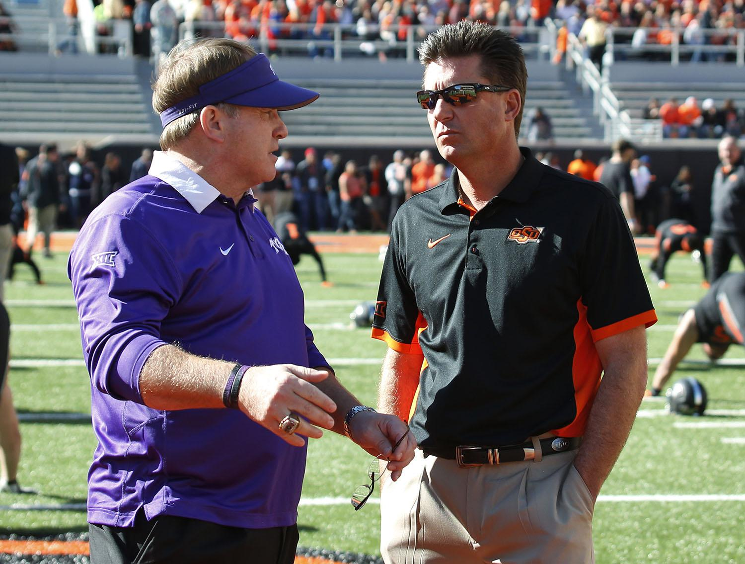 TCU head coach Gary Patterson, left, and Oklahoma State head coach Mike Gundy, right, talk before the start of an NCAA college football game in Stillwater, Okla., Saturday, Nov. 7, 2015. (AP Photo/Sue Ogrocki)