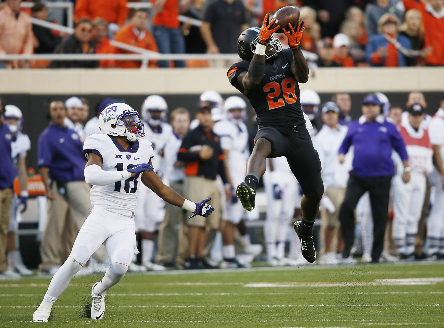 Oklahoma State wide receiver James Washington (28) leaps up for a pass in front of TCU safety Nick Orr (18) in the third quarter of an NCAA college football game in Stillwater, Okla., Saturday, Nov. 7, 2015. Washington took the pass into the end zone for a touchdown and Oklahoma State won 49-29. (AP Photo/Sue Ogrocki)