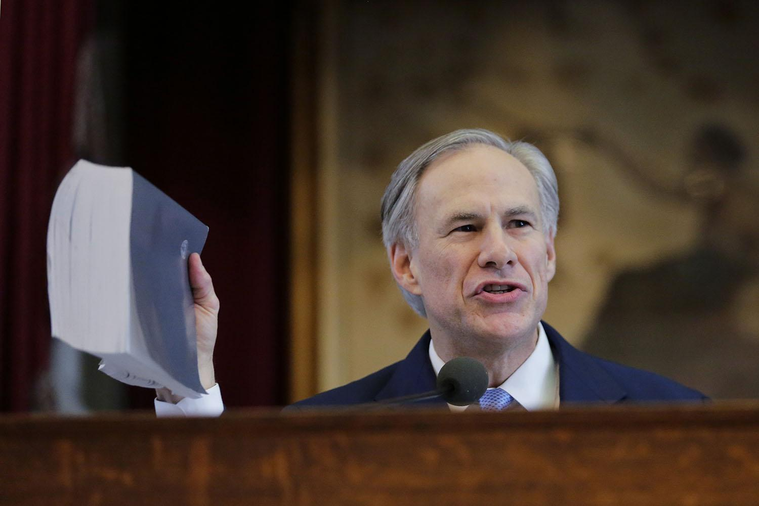Texas Gov. Greg Abbott holds a book about Texas school laws as he delivers his State of the State address to a joint session of the House and Senate, Tuesday, Feb. 17, 2015, in Austin, Texas. (AP Photo/Eric Gay)
