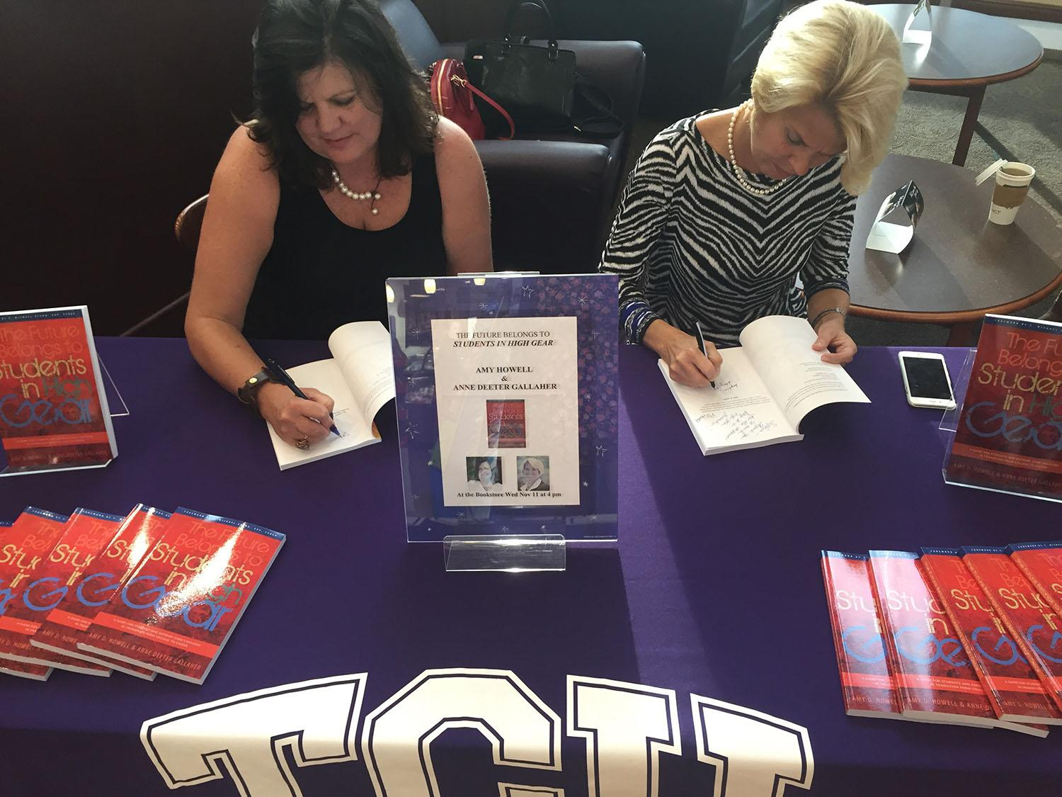 "Authors Amy Howell (left) and Anne Gallaher (right) signing copies of their book ""Students in High Gear"""