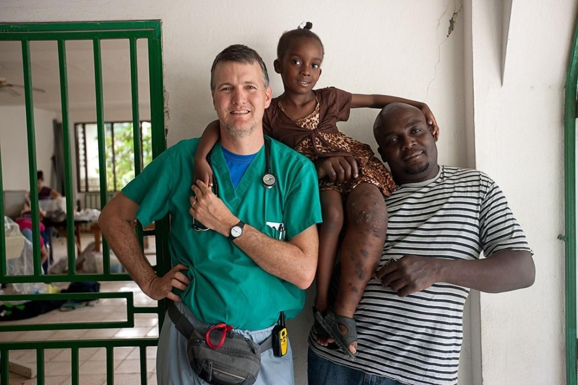 Dr. Ric  Bonnell poses with Ruth and Moliere Jacques in Haiti. They lived with the Bonnells in Texas for a few months while she was receiving therapy for her leg malformation.