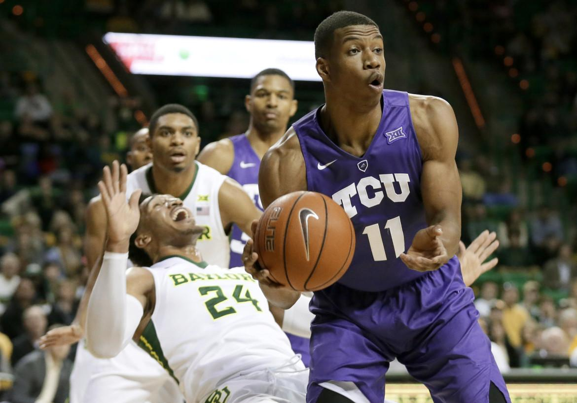 TCU guard Brandon Parrish (11) passes the ball after collecting an offensive rebound in front of Baylor's Ishmail Wainright (24) in the first half of an NCAA college basketball game on Jan. 13 in Waco, Texas.