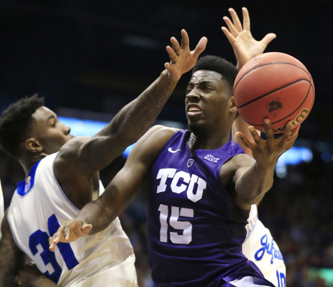 TCU forward JD Miller (15) shoots while pressured by Kansas forward Jamari Traylor (31) and guard Sviatoslav Mykhailiuk (10) during the second half of an NCAA college basketball game in Lawrence, Kan., on Jan. 16.