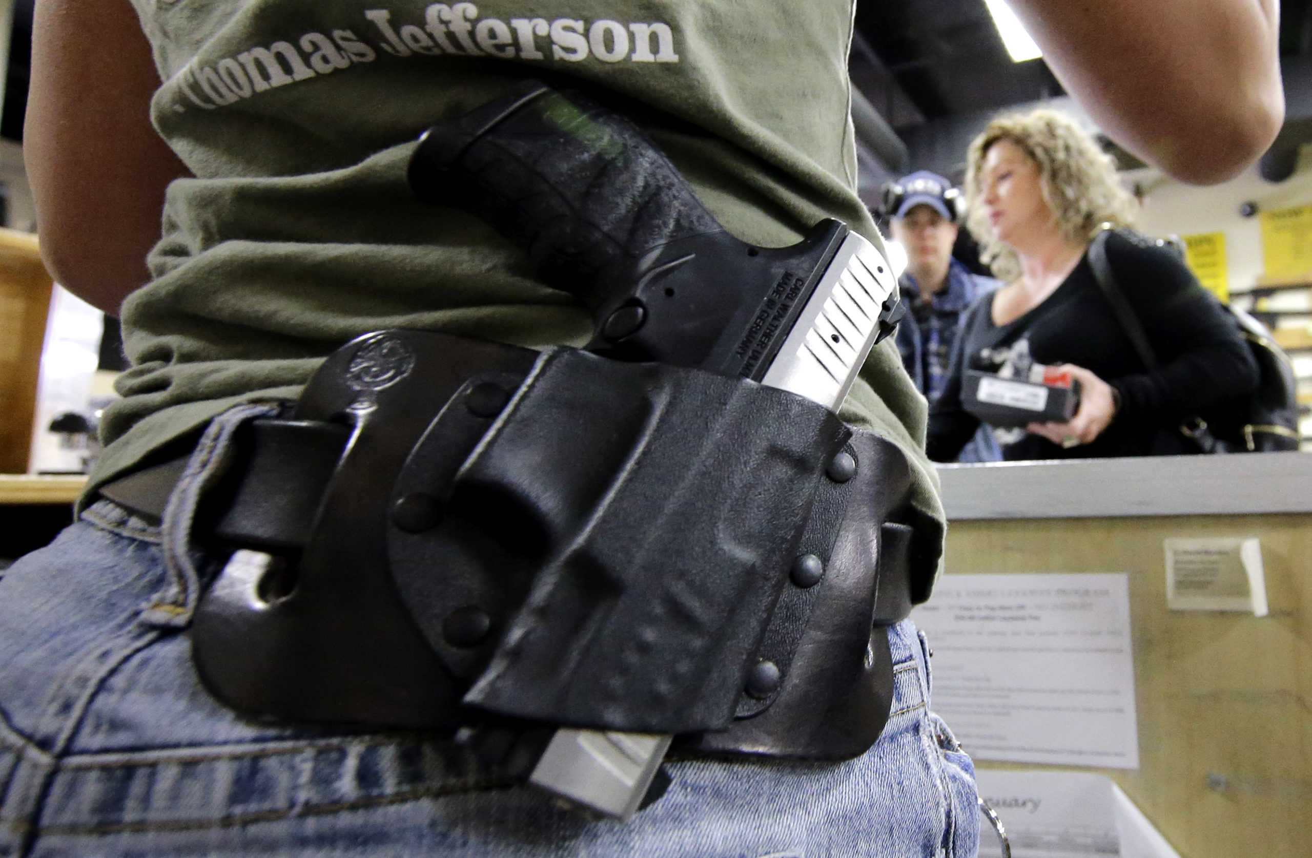 Kayla Brown, left, wears her gun on her hip while working at the Spring Guns and Ammo store Monday, Jan. 4, 2016, in Spring, Texas. (AP Photo/David J. Phillip)