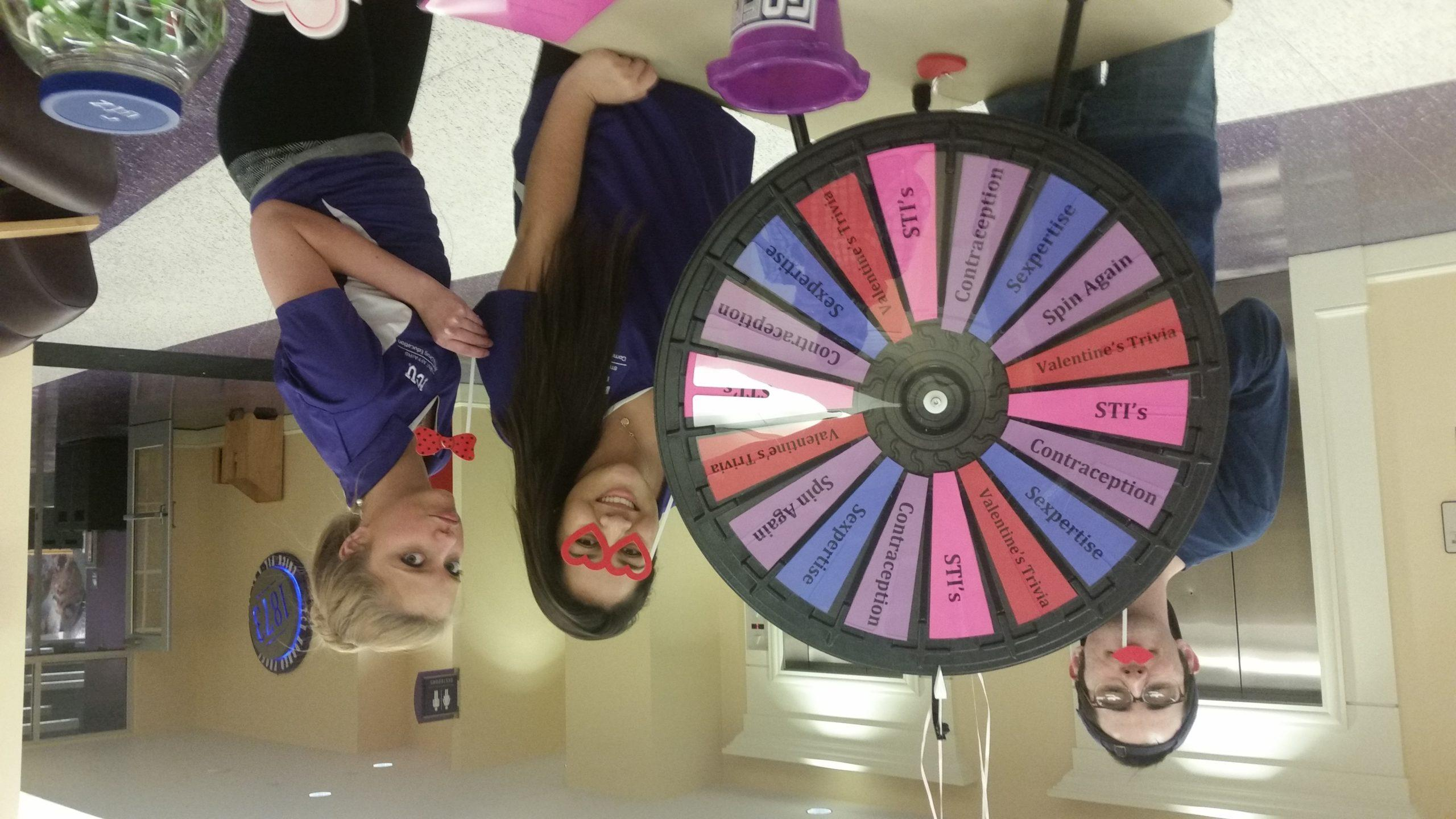 Three student volunteers helping with Sexual awareness event.