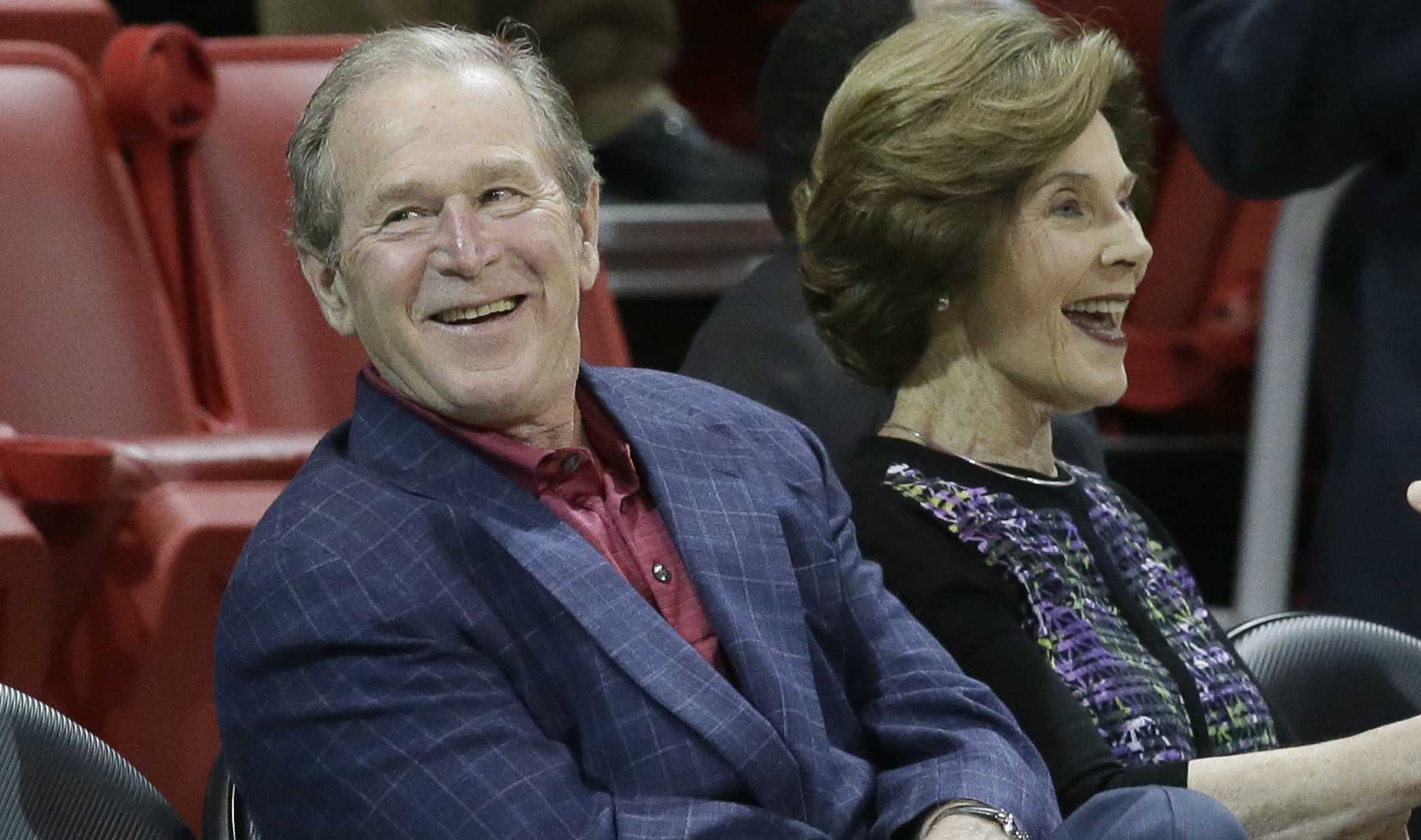 Former President George W. Bush sits with his wife Laura Bush before an NCAA college basketball game between Tulsa and SMU Wednesday, Feb. 10, 2016, in Dallas. (AP Photo/LM Otero)