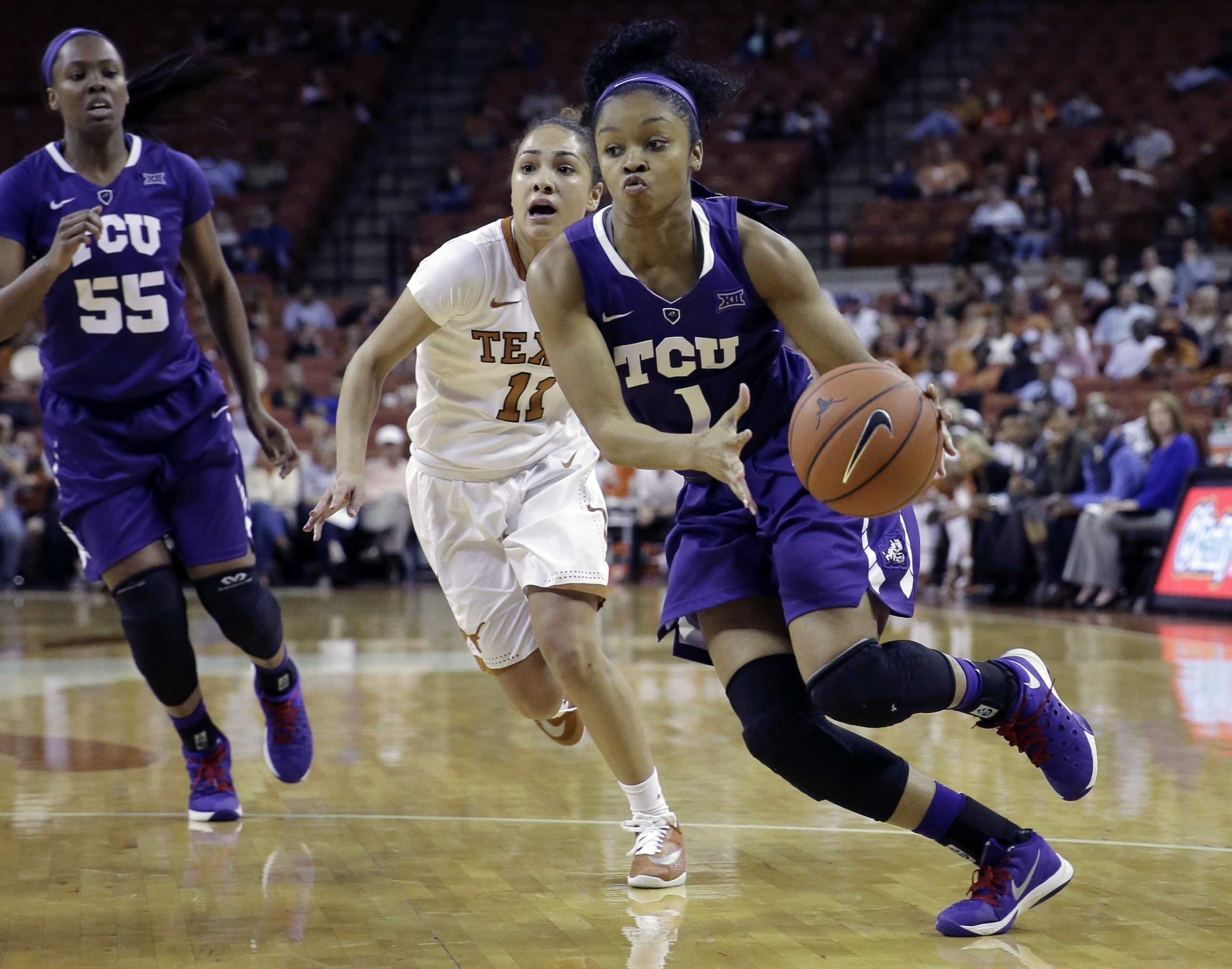 TCU guard Toree Thompson (1) drives around Texas guard Brooke McCarty (11) on Feb. 27 in Austin.