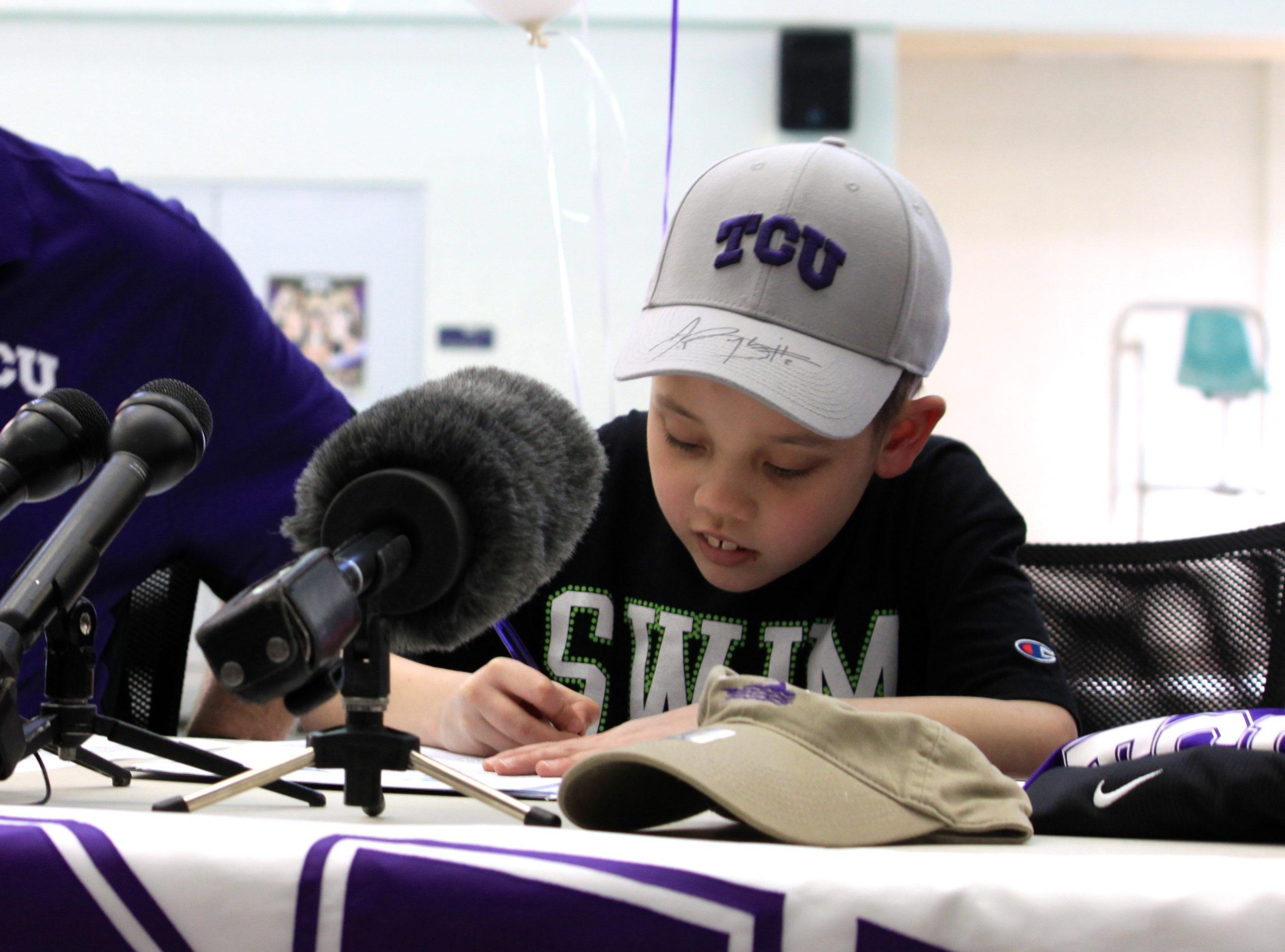 Eight-year-old Nathan Lin signs to become an honorary member of the TCU swimming & diving program.