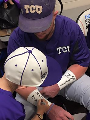 Micah Ahern signs his name on TCU catcher Evan Skoug's wristbands before the Frogs' game against Coastal Carolina in Omaha, Neb. on June 21.