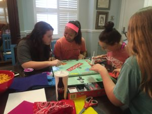 Sorority members gather around a table to create texturized board games for blind children at the Delta Gamma house (Nicole Strong/TCU360).