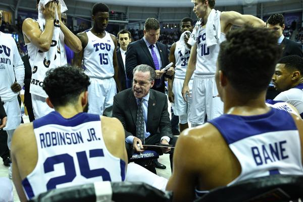 TCU head coach Jamie Dixon talks strategy with his team during a timeout. (Photo courtesy of GoFrogs.com)